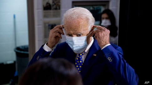 Democratic presidential candidate former Vice President Joe Biden puts on his mask as he leaves a campaign event