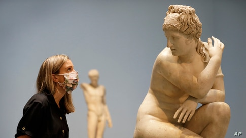 A museum employee looks towards a marble statue of Crouching Venus, Roman, 2nd century AD, during a press view at The British…