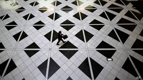 A man wearing a face mask to help curb the spread of the coronavirus walks at a building in Tokyo, Thursday, Aug. 27, 2020. (AP…