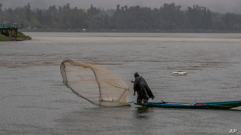 A Kashmiri fisherman casts his net as it rains at the Dal Lake on the outskirts of Srinagar, Indian controlled Kashmir,…