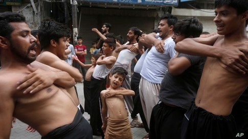 A Shiite Muslim boy beat his chest with others during a Muharram procession, in Lahore, Pakistan, Friday, Aug. 28, 2020…