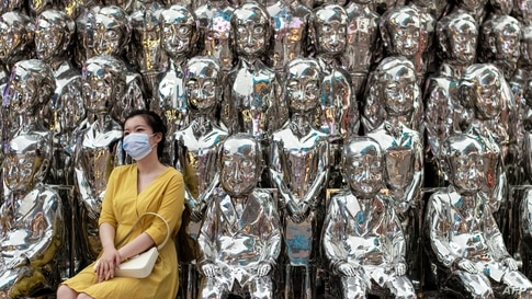 A woman wearing a face mask poses for a picture at a shopping centre in Beijing, China.