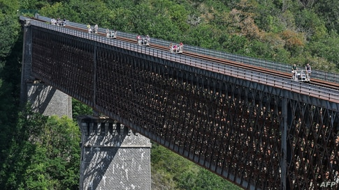 People cross the Viaduc des Fades as they ride the 'vélorail' on an old railway line in Les Ancizes-Comps, central France, Aug. 18, 2020.
