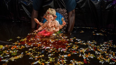 A volunteer immerses a clay idol of Hindu elephant-headed deity Ganesh in an artificial tank in Mumbai, India.