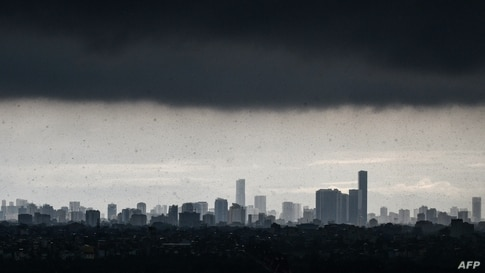 Dark clouds loom over the Hanoi skyline during a heavy downpour, Vietnam.
