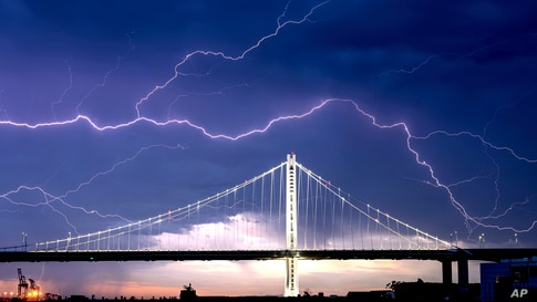 Lightning forks over the San Francisco-Oakland Bay Bridge as a storm passes over Oakland, California.