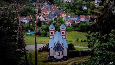A chapel stands on a hill over the city of Mespelbrunn in the Spessart region, Germany, Aug. 29, 2020.