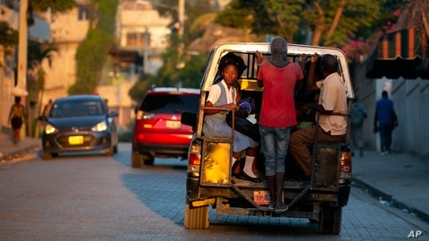 """Students ride to school in a """"tap-tap,"""" a vehicled used for public transportation, in Port-au-Prince, Haiti."""