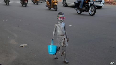 A young boy with his body painted and dressed as Mahatma Gandhi seeks alms at a traffic intersection in Hyderabad, India.