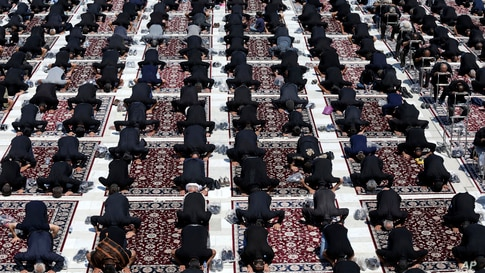 People attend the noon prayer during an annual mourning ceremony commemorating Ashoura, at the courtyard of the Saint Abdulazim shrine in Shahr-e-Ray, south of Tehran, Iran.