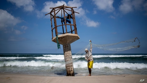 A Palestinian fisherman cleans up his fishing net after the Israeli decision to close Gaza's fishing zone, on the beach in Gaza City.