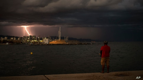 A man is fishing as lightning flashes in the night sky during a storm in Barcelona, Spain, Aug. 30, 2020.