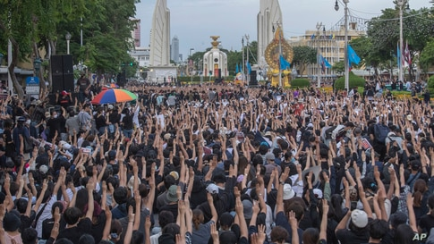 Pro-democracy students raise three-fingers, symbol of resistance salute, during a rally in Bangkok, Thailand.