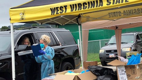 Parents and students arrive in their vehicles for health screenings and temperature checks before moving into residence halls at West Virginia State University campus, July 31, 2020, in Institute, West Virginia.