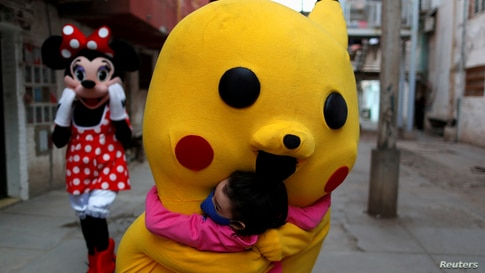 A volunteer wearing a costume of Pokemon character Pikachu hugs a child during Children's Day, in Fuerte Apache, in Buenos Aires, Argentina, Aug. 16, 2020.