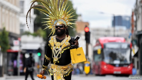 A festival goer dances in a street after the Notting Hill Carnival festivities were cancelled amid the coronavirus disease (COVID-19) outbreak, in London.