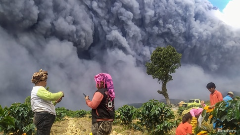 Locals harvest their potatoes as Mount Sinabung spews volcanic ash in Karo, North Sumatra province, Indonesia.