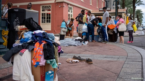 Evacuees displaced by Hurricane Laura look through items that had been dropped off on the curb outside of the New Orleans Marriott in New Orleans, Louisiana, Aug. 30, 2020.