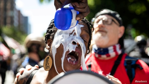 A woman has her eyes flushed after being affected by tear gas during a protest against racial injustice in Portland, Oregon, Aug. 22, 2020.
