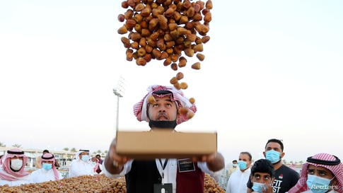 A farmer throws dates in the air during Unaizah Season for Dates, at Unaizah city in Al-Qassim province, Saudi Arabia.