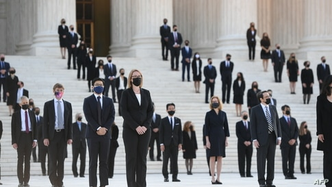 People wait for the casket of the late Supreme Court Justice Ruth Bader Ginsburg to arrive at the US Supreme Court in…