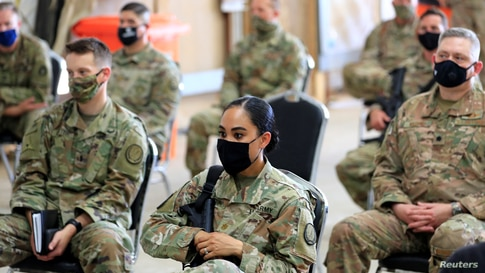 U.S. soldiers wearing protective masks are seen during a handover ceremony of Taji military base from US-led coalition troops…