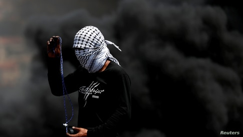 A Palestinian demonstrator uses a sling to hurl stones at Israeli troops during a protest against Jewish settlements, in Kafr…