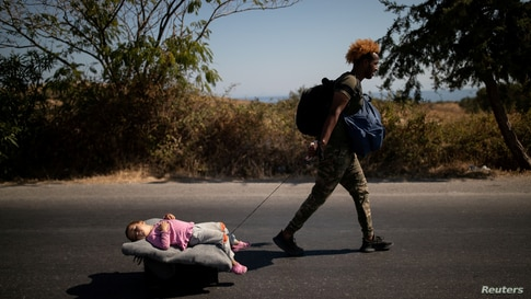 A migrant pulls a girl lying on a cart, following a fire at the Moria camp on the island of Lesbos, Greece, September 11, 2020…