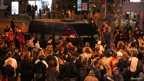 People surround a police van during an opposition protest against the inauguration of Belarusian President Alexander Lukashenko.
