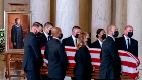 The flag-draped casket of Justice Ruth Bader Ginsburg, carried by Supreme Court police officers, arrives in the Great Hall