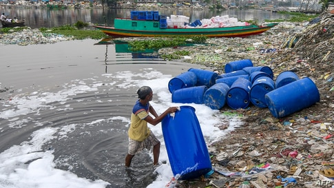 A worker cleans barrels used to contain chemicals in Buriganga river in Dhaka, Bangladesh.