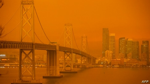 The San Francisco Bay Bridge and city skyline are obscured in orange smoke and haze as seen from Treasure Island in San Francisco, California, Sep. 9, 2020.