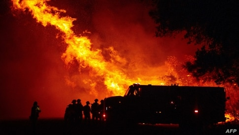 Butte county firefighters watch as flames tower over their truck at the Bear fire in Oroville, California.
