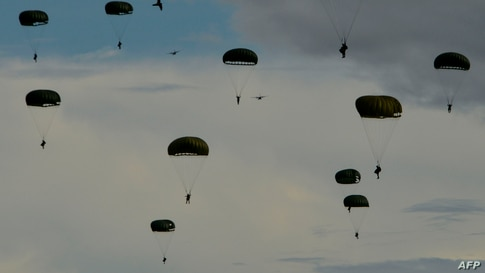 Indonesian paratroopers descend with their chutes during the Jalak Sakti military exercise held at the Sultan Iskandar Muda Air Force Base in Blang Bintang, Aceh province.
