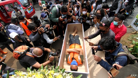 A man, who gets caught not wearing a face mask in public amid the COVID-19 pandemic, lies in a mock coffin as part of punishment by local authorities in Jakarta, Indonesia.