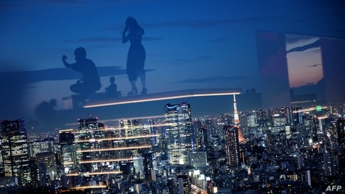 The Tokyo Tower (centre R) is illuminated as visitors are reflected in glass while visiting the Shibuya Sky observation deck in Tokyo, Japan.