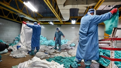 Workers handle dirty laundry from the COVID-19 zone, in the laundry room of the Mexican Institute of Social Security (IMSS), in Mexico City.