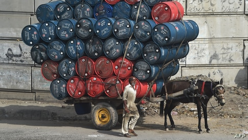 A man stands next to a horsecart laden with oil drums on a street in Lahore, Pakistan.