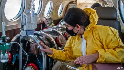 Andrea Lara (R) looks at her father Juan Carlos Lara, 59, a patient with COVID-19, as he is transferred inside a security capsule on an air ambulance from Iquitos to the Intensive Care Unit of the Rebagliati Hospital, in Lima, Peru.