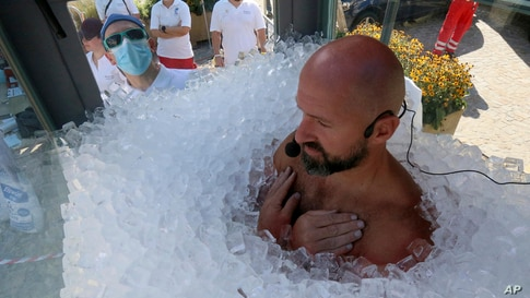 Austrian ice swimmer Josef Koeberl is standing in a glass cabin filled with ice to break the world record for a human to stay side an ice box in Melk, Sept. 5, 2020.