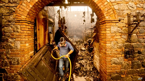 Cellar worker Jose Juan Perez extinguishes hotspots at Castello di Amorosa, Sept. 28, 2020, in Calistoga, California, which was damaged in the Glass Fire.