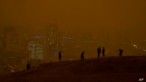 People look at the skyline obscured by wildfire smoke during daytime from Kite Hill Open Space in San Francisco, California.