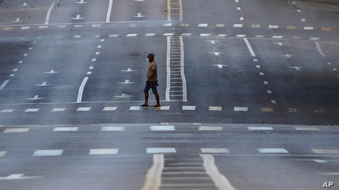 A man walks on an empty street during curfew in Havana, Cuba, Sept. 1, 2020. Authorities launched a strict 15-day lockdown in the capital in order to stamp out the low-level but persistent spread of the novel coronavirus.