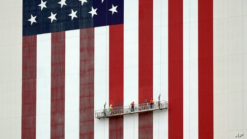 Workers apply fresh paint to the flag on the side of the Vehicle Assembly Building at the Kennedy Space Center in Cape Canaveral, Florida.