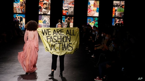An activist displays a banner during Dior's Spring-Summer 2021 fashion collection presented during the Paris fashion week in Paris, France.