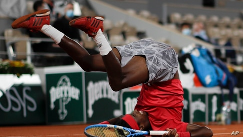 Mikael Ymer of Sweden slips and falls in the first round match of the French Open tennis tournament against Serbia's Novak Djokovic at the Roland Garros stadium in Paris, France.