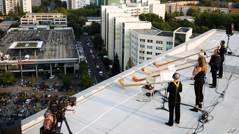 Musicians with alp horns perform on the roof of an apartment block in the Prohlis neighborhood in Dresden, Germany, Sept. 12, 2020.
