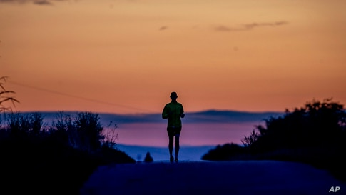 A man runs on a small road in the outskirts of Frankfurt, Germany, before sunrise.