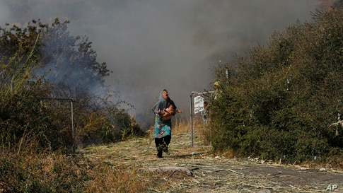 A migrant holds her baby as she runs from a small fire in a field near Mytilene town, on the northeastern island of Lesbos, Greece, Sept. 12, 2020.