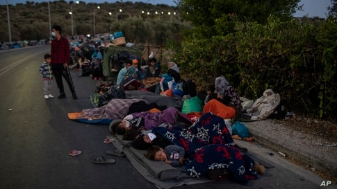 Migrants sleep on the road near the Moria refugee camp on the northeastern island of Lesbos, Greece after a second fire in the camp destroyed nearly everything.